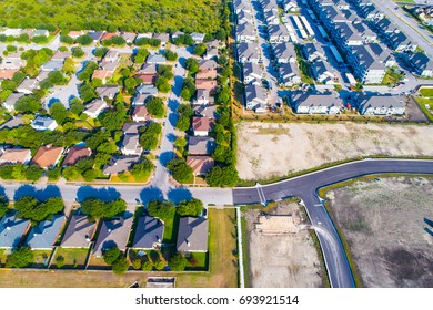 Aerial drone view above homes in suburb and rows of large luxury condo apartments with a new square development area construction zone for new houses