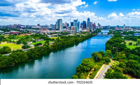 Aerial drone view above Lady Bird Lake in Austin Texas with city skyline in background on a wonderful summer day blue sky green landscape and fresh cold spring swimming hole water