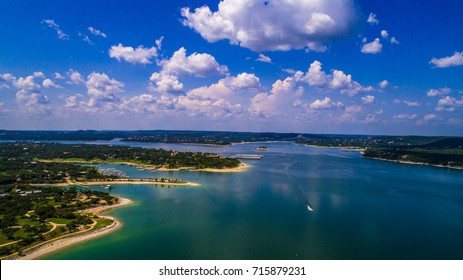 Aerial drone view above Lake Travis a paradise of clear blue water and relaxation right outside Austin Texas an amazing summer landscape on the lake with boat racing across water