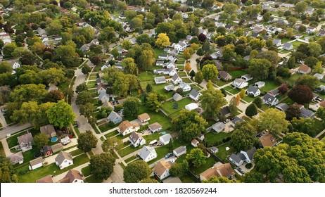 Aerial drone view of American suburban neighborhood at daytime. Establishing shot of America's  suburb. Residential single family houses pattern
