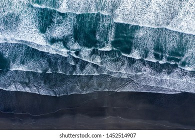 Aerial drone view of Atlantic ocean waves washing black basaltic sand beach, Iceland