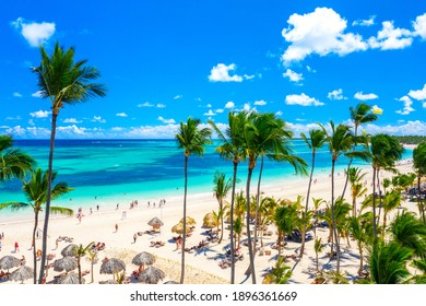 Aerial drone view of beautiful atlantic tropical beach with palms, straw umbrellas and boats. Bavaro, Punta Cana, Dominican Republic. Vacation background