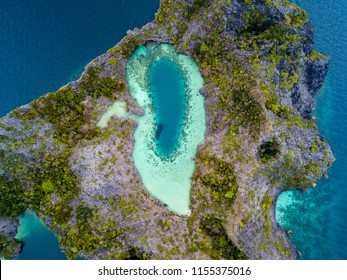 Aerial drone view of a beautiful coral lagoon inside a remote tropical island (Shark Lagoon, Cock Comb Island, Myanmar)