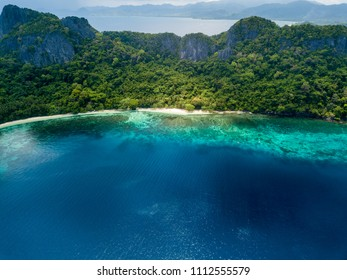 Aerial drone view of a beautiful deserted tropical beach surrounded by large cliffs and jungle (Cadlao Island, El Nido, Palawan)