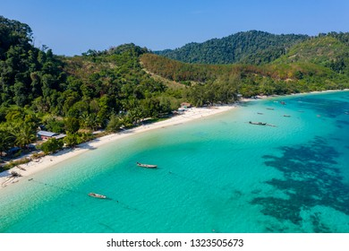 Aerial drone view of a beautiful tropical island surrounded by coral reefs and covered with lush, green jungle (Kyun Phi Lar, Myanmar)