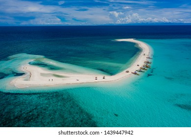 Aerial drone view of a beautiful white sandbar surrounded by coral reef near a tropical island (White Island, Camiguin)