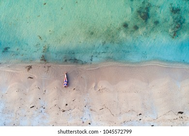 aerial drone view of beautiful, young woman with blue bikini on a great beach in thailand, koh samui