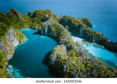 Aerial drone view of Big lagoon surrounded by jagged limestone karst cliffs in morning soft light just before tourist arrive. El Nido, Palawan Philippines
