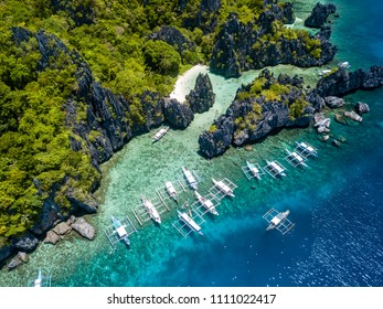 Aerial drone view of boats over a tropical coral reef and remote sandy beach (Hidden Beach, El Nido)