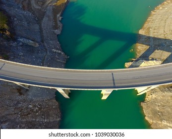 Aerial drone view of bridge over turquoise waters in Llosa del Cavall Lake, near Barcelona, Catalonia, Europe. Dry lake for climate change warming. Beautiful, bridge adventure and travel
