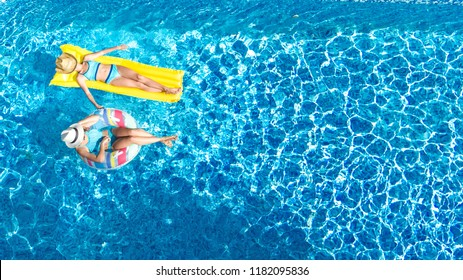 Aerial drone view of children in swimming pool from above, happy kids swim on inflatable ring donut and mattress, girls have fun in water on family vacation on holiday resort