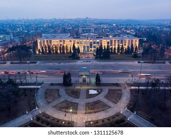 Aerial drone view of chisinau city center at night with light and blue sky, government building and arch, Moldova