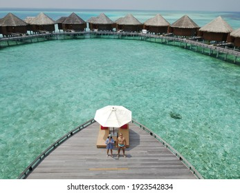 Aerial drone view of a couple on a wooden deck in the Maldives, with a stunning turquoise sea with cristal clear waters and overwater bungalows.