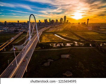 Aerial drone view of Dallas , Texas skyline cityscape high above skyscrapers and modern suspension bridge over trinity river park with amazing sunrise in background of downtown