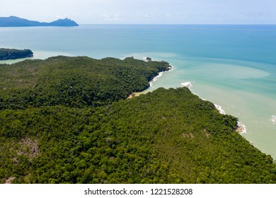 Aerial drone view of dense tropical rainforest leading to a remote, rough ocean coastline
