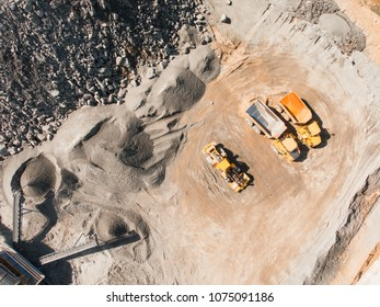 Aerial drone view of excavator loading the tipper truck at the construction site, open pit mine, extractive industry