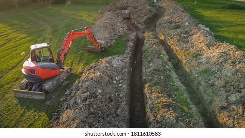 Lufttrockner-Sicht auf Erdwärme-Kollektorgrube oder Graben im Boden. Ausgrabung von Graben oder Löchern für den Wärmeaustauscher für ein Haus. Bagger auf Arbeit