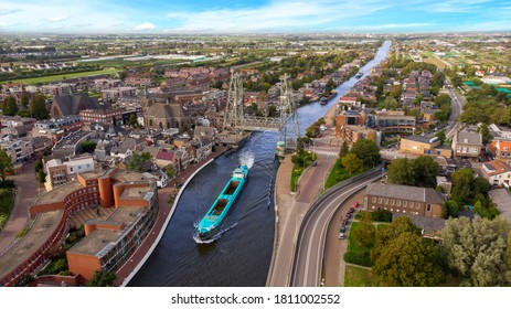 Aerial drone view of the Gouwe canal with a historical lift bridge (Dutch: Hefbrug) in Boskoop opened for some cargo ships coming from the inland terminal of Alphen aan den Rijn called 'Alpherium'.