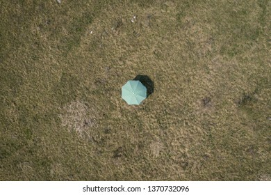 Aerial drone view of a green sun umbrella on a meadow