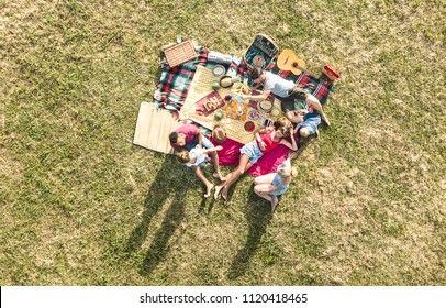 Aerial drone view of happy families having fun with kids at picnic barbecue party - Multiracial happiness and love concept with mixed race people playing with children at park - Warm bright filter