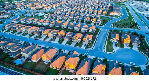 Aerial drone view high above rows and square cookie cutter houses in north Austin Texas near Round Rock , a growing suburb of ATX , with cup de sac and sunset colors on rooftop of suburbia
