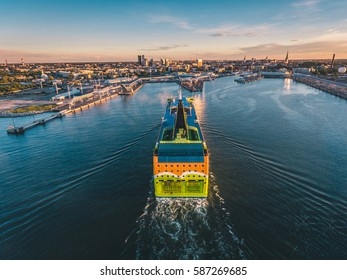 Aerial drone view of the huge cruise ferry arriving to the port of Tallinn at sunset with a Tallinn cityscape view on the background