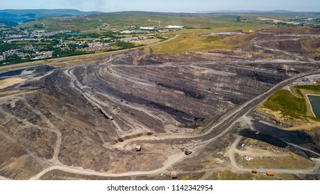 Aerial drone view of a huge opencast coal mine cut into a rural hilly area (Dowlais, Merthyr Tydfil, Wales)