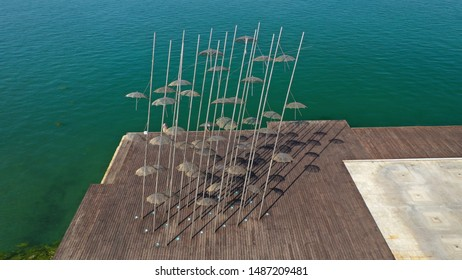"""Aerial drone view of iconic and famous """"Umbrellas"""" in promenade area of new waterfront of Thessaloniki or Salonica featuring iconic Alexander the Great statue, North Greece"""