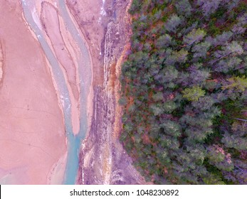 Aerial drone view of landscape in geology and hydrogeology, natural risk of flooding. Reservoir and dry lake Beautiful scene of half large pine forest and half rocks and water. Climate change.