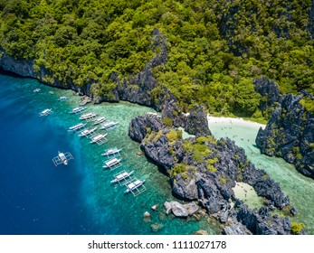 Aerial drone view of large numbers of tourist boats next to a tropical lagoon and beach in El Nido, Palawan