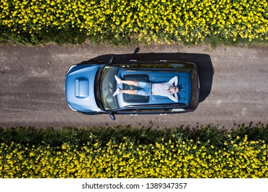 Aerial drone view of man relaxing on car roof. Male enjoying sun and taking a break during travel