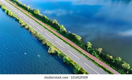 Vista aérea por drones de la carretera y del camino de ciclismo en la represa de polder, tráfico de camiones desde arriba, Holanda del Norte, Países Bajos