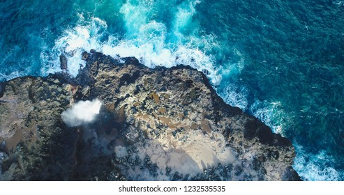 An aerial drone view of the Nakalele Blowhole, a powerful ocean blowhole shooting up between lava formations, including a heart-shaped rock, in West Maui near Wailuku.