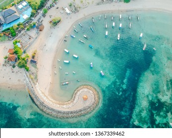 Aerial drone view of ocean, boats, beach, shore In Sanur Beach, Bali, Indonesia with with Traditional Balinese Fishing Boats amazing blue ocean.