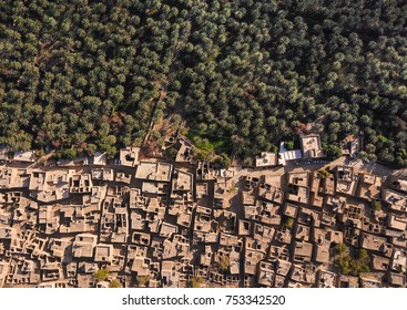 Aerial drone view of an old traditional Omani mud village in the mountains among date palm trees. Al Hamra, Oman.