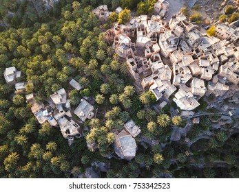 Aerial drone view of an old traditional Omani mud village in the mountains among date palm trees. Misfat Al Aberyeen, Oman.