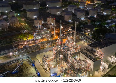 Aerial drone view over huge oil refinery factory at night with many storage tank and distillation tower pipeline in Bangkok Thailand can use for energy or industrial concept.