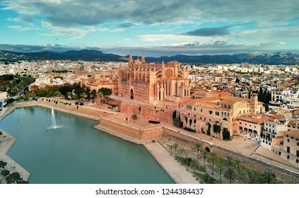 Aerial drone view Palma de Majorca Cathedral was built on a cliff rising out of the sea. Picturesque panorama Majorca cityscape mountain range cloudy sky residential buildings from top. Spain
