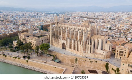 Aerial drone view Palma de Mallorca Cathedral was built on a cliff rising out of the sea. Picturesque panorama Majorca cityscape mountain range cloudy sky residential buildings from top. Spain