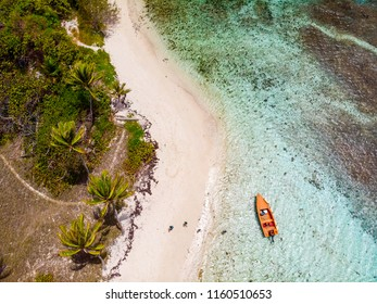 Aerial drone view of Petit Tabac tropical island, turquoise Caribbean sea of Tobago cays, and a family with kids in St Vincent and Grenadines