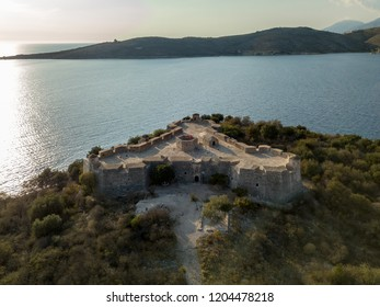 Aerial drone view of Porto Palermo Castle in Himara, Albania at sunset in autumn with sea and mountain in background