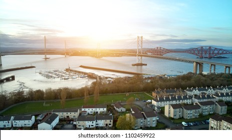 Aerial drone view of The Queensferry Crossing bridges over the Firth of Forth and houses, Edinburgh, Scotland, UK.