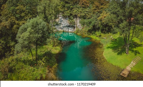 Aerial drone view of river source or spring of Krupa in Bela Krajina (White Carniola) in Slovenia on a misty cloudy day. Visible leaves and foggy green river with rock formation in the back. - Shutterstock ID 1170219409