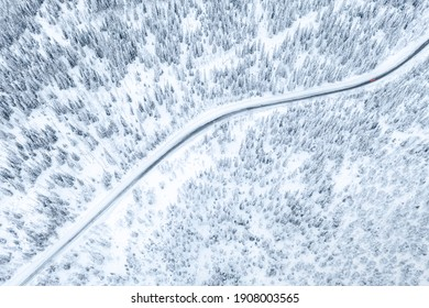 Aerial drone view of road in winter forest with red car