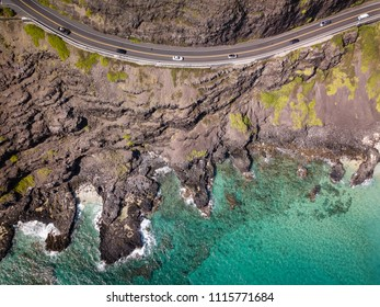 Aerial drone view of rocky Makapuu Point coastal landscape and highway with cars on Oahu, Hawaii, USA.
