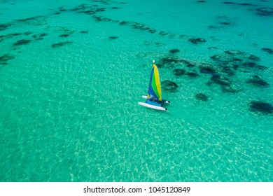 Aerial drone view of sailing sailboat surf or catamaran in turquoise water of Caribbean sea near Punta Cana beach.