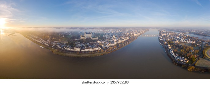 Aerial drone view of Saumur skyline with the medieval castle, Saint Peter church and the Loire river at sunrise.