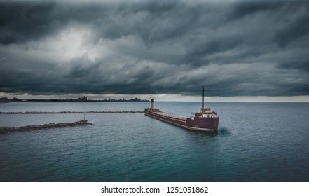 Aerial drone view from a second angle  of an abandoned old and rusty shipwreck on a stormy day, Lake Ontario, Canada