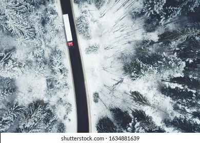 Aerial drone view of semitrailer truck and lorry drive along the road through the winter forest. Transportation on icy road.