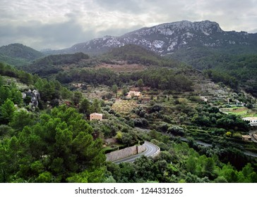 Aerial drone view of small hillside Banyalbufar town on west coast of Mallorca. Surrounded by Tramuntana mountain range district nestles among smaller peaks, where scattered farms and vineyards. Spain